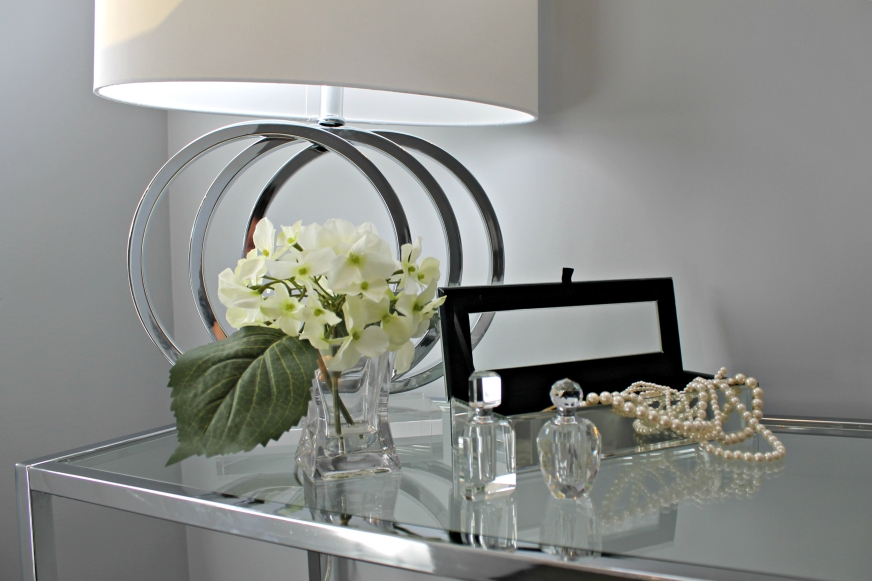 staged glass table with a lamp, perfume and pearls
