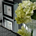 clock on nightstand with flowers staging